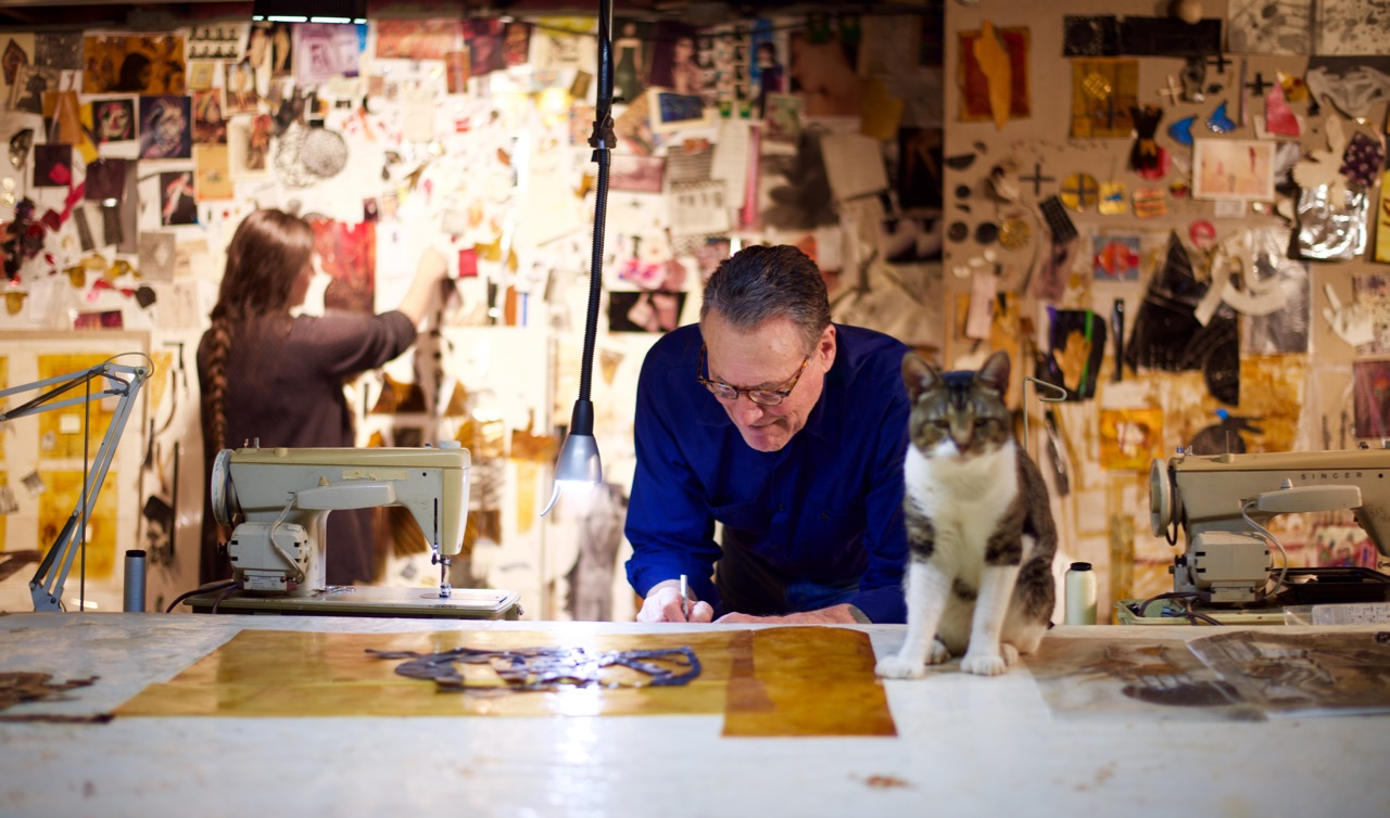 Chris Pekoc, Artist, working at his drawing table. Cat sitting on table.