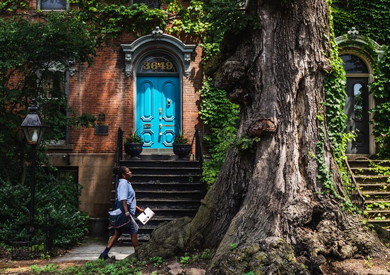 Postal worker walking by brownstone apartment with bright blue door.