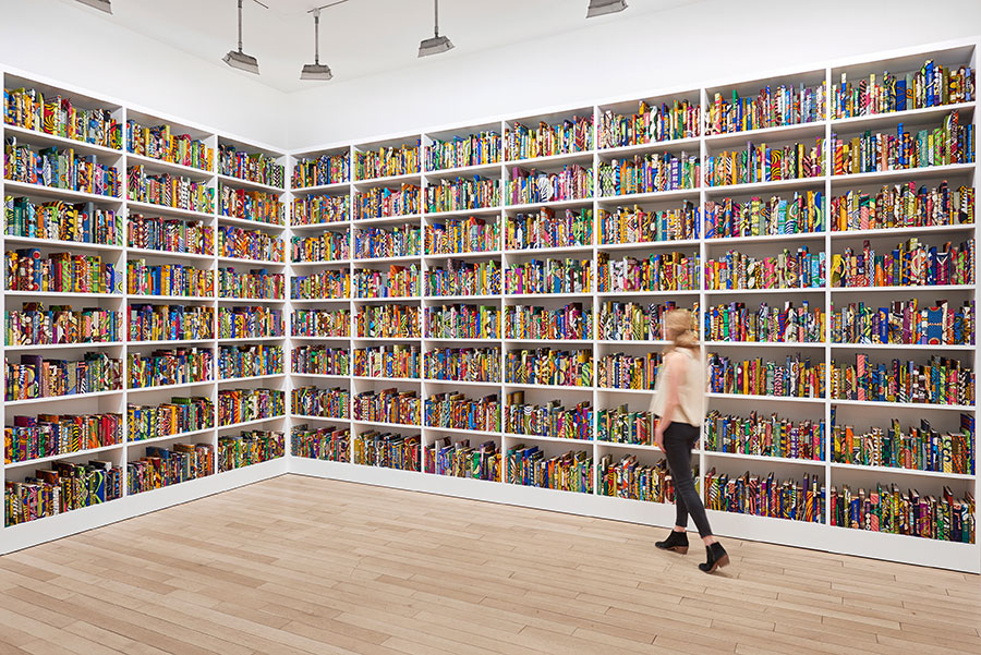 Floor to ceiling shelves of books. The British Library 2014 Hardback books, past work of Yinka Shonibare