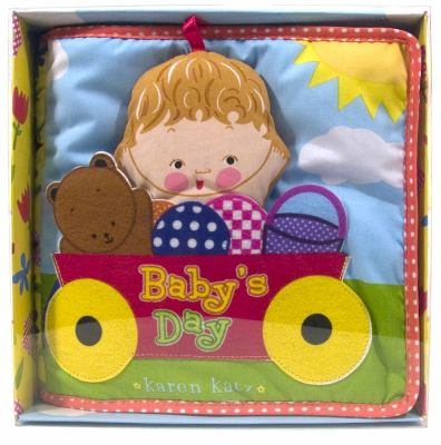 Baby's Day cloth book jaket of a artoon baby's large head and a teddy bear in a red wagon with yellow wheels.