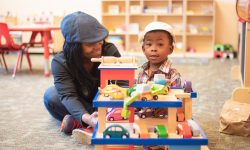 Woman and a child playing with a toy house at Woodland Branch.