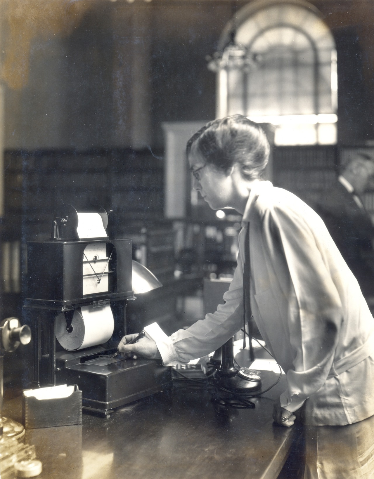 A Library employee using the Telautograph machine, an early precursor to the fax machine, ca. 1925.