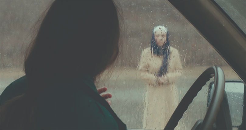 Old woman with white hair seen through a wet and foggy car window