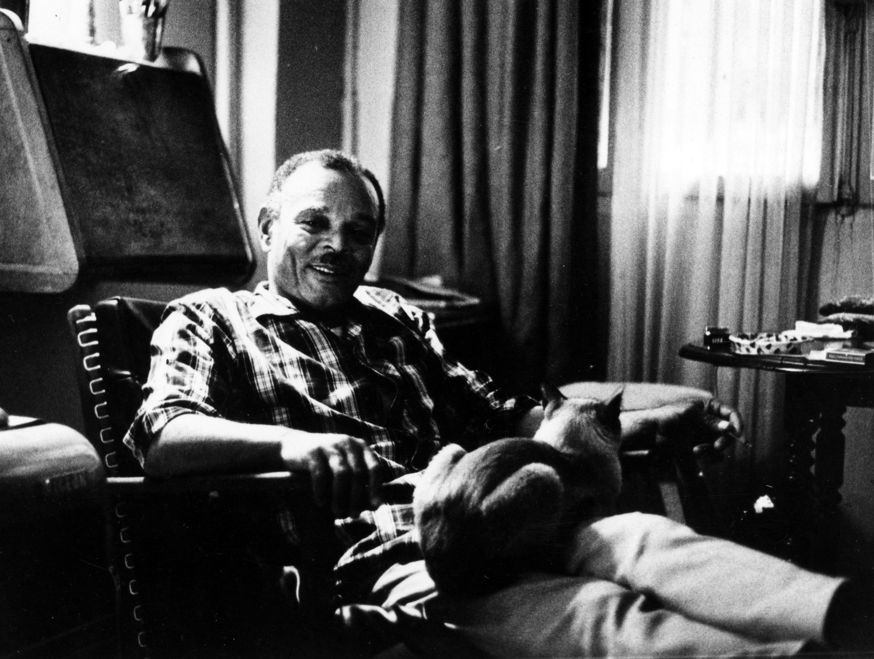 Chester B. Himes in a lounge chair, black and white photo, with a cat on his lap.