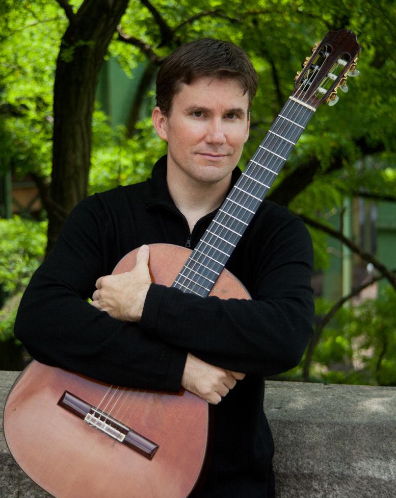 Musician Peter Fletcher holding a guitar