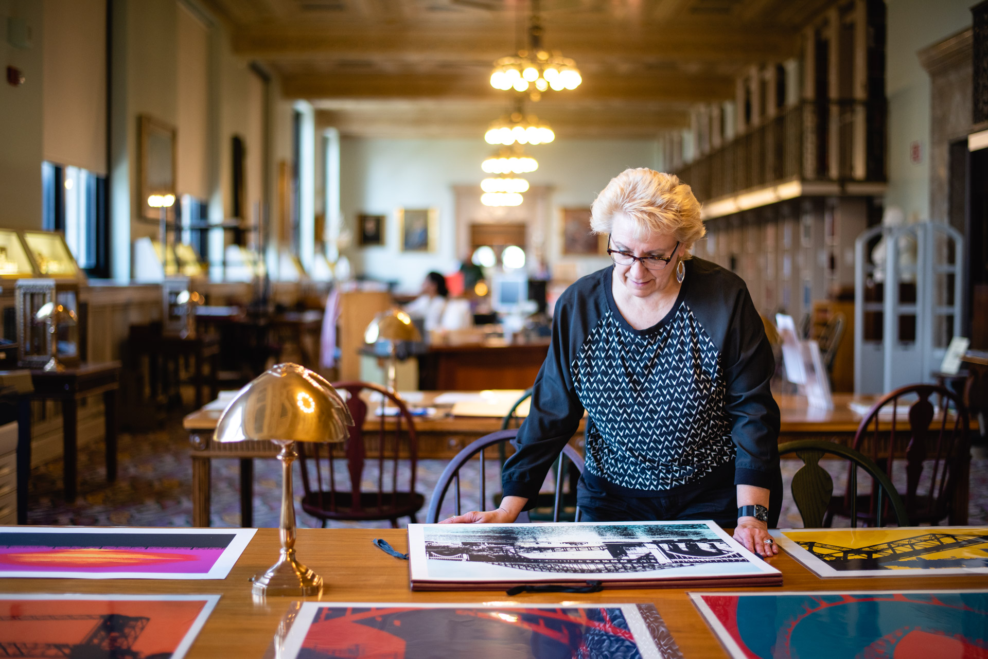Pam Eyerdam (blond haired woman) standing at a table, looking at large art prints in the Special Collections Department.