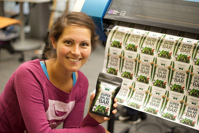 Photograph of Renee Volchko with a display of her product Super Salad Bar