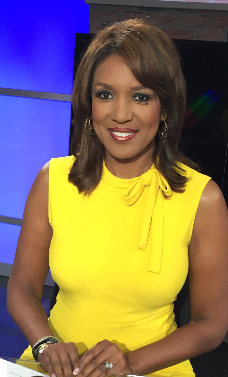 Portrait of local television news anchor Ramona Robinson in a yellow blouse with blue light coming through a window behind her.