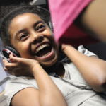 Young girl wearing headphones laughing excitedly