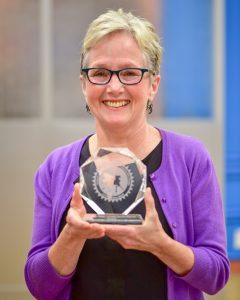 Woman with short hair and glasses holding a circular crystal award
