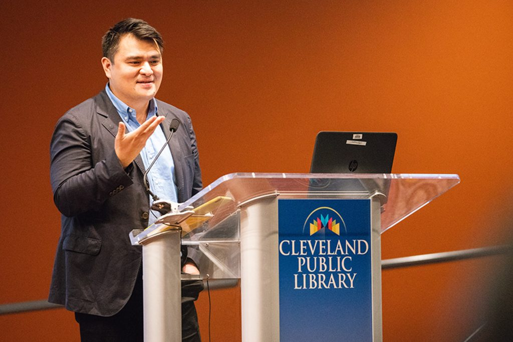 Closeup of Jose Antonio Vargas in a blazer and buttoned shirt presenting from behind a lectern