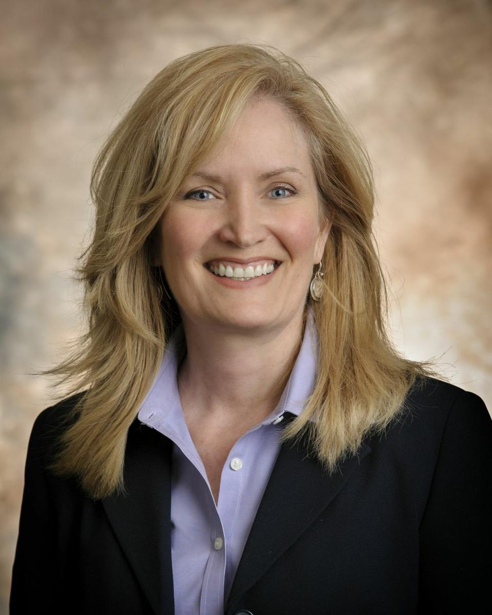 Head and shoulders shot of Tena Wilson, with long blond hair, wearing a blue suit.