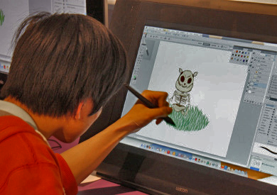 Teen drawing a digital cartoon character on a computer screen