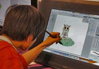 Teen drawing a digital cartoon character on a computer screen