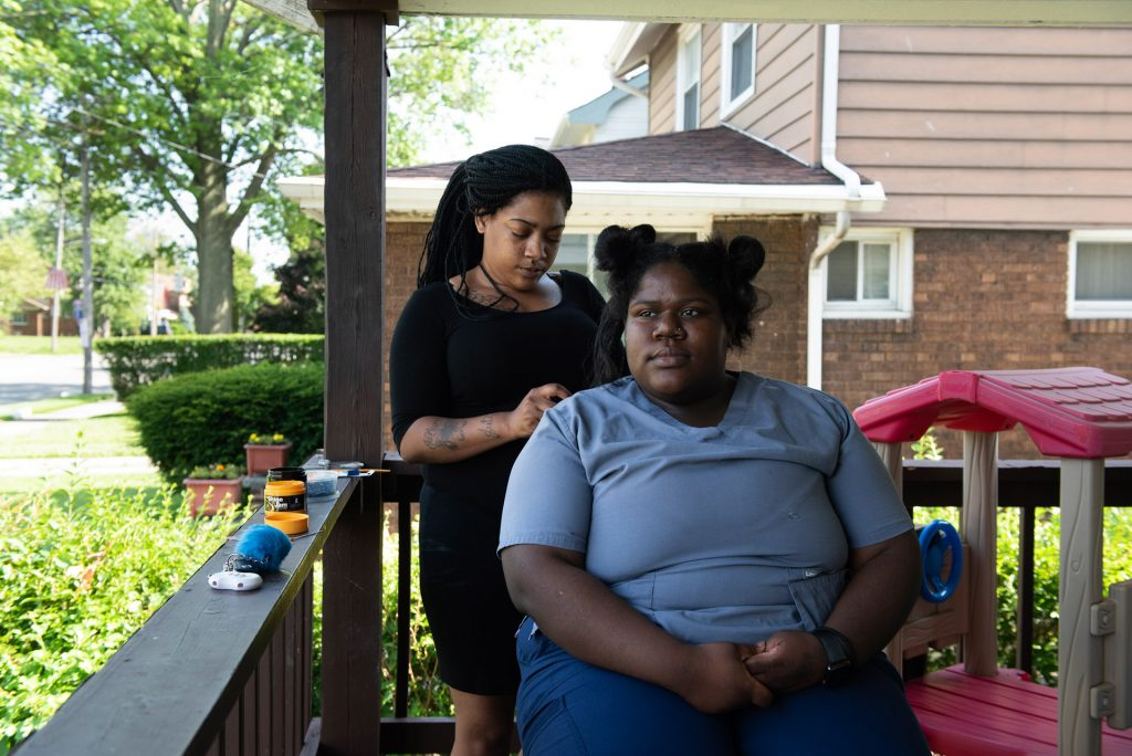 A woman braiding another woman's hair while sitting on a shaded porch in the Collinwood Neighborhood.