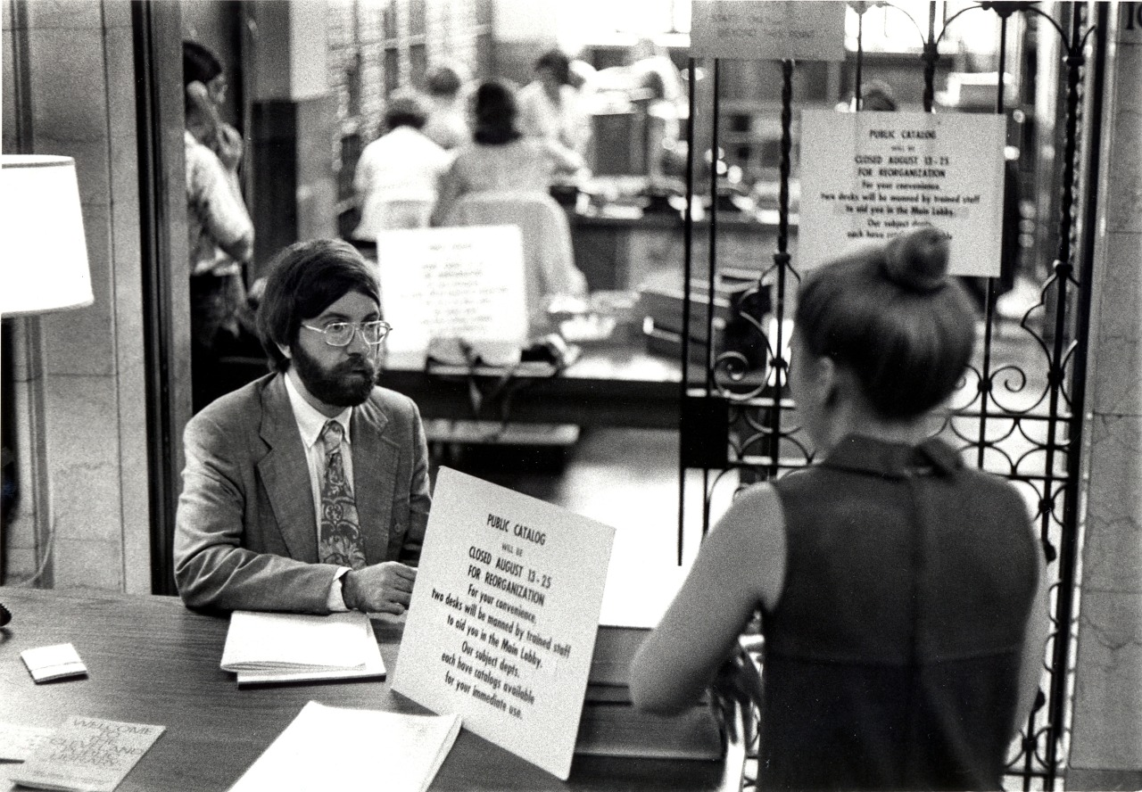 Black and white photograph of a library employee seated behind one of the Public Catalog service desks while helping a patron