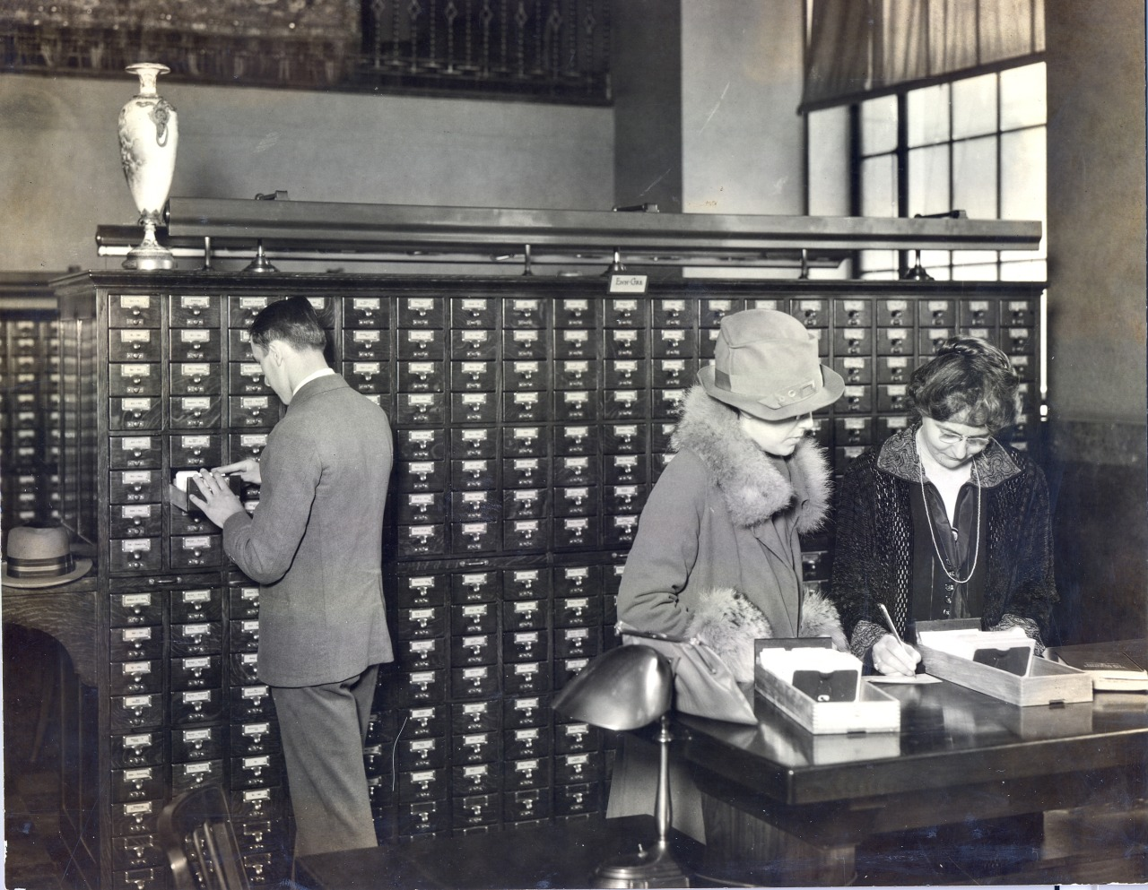 Black and white photo in mid-1920s shows several patrons finding books with the use of the card catalog.