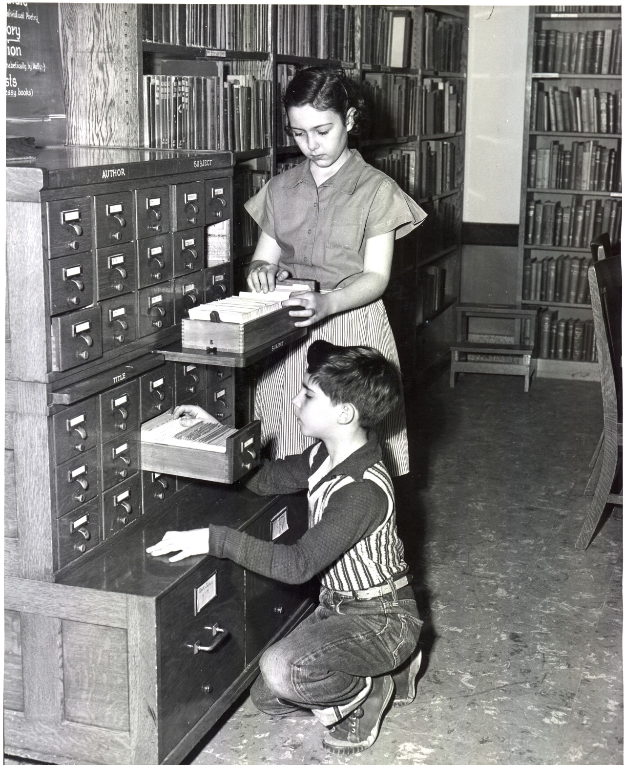 Black and white photo of a girl and boy at Hazeldell Elementary School Library, taken in 1953