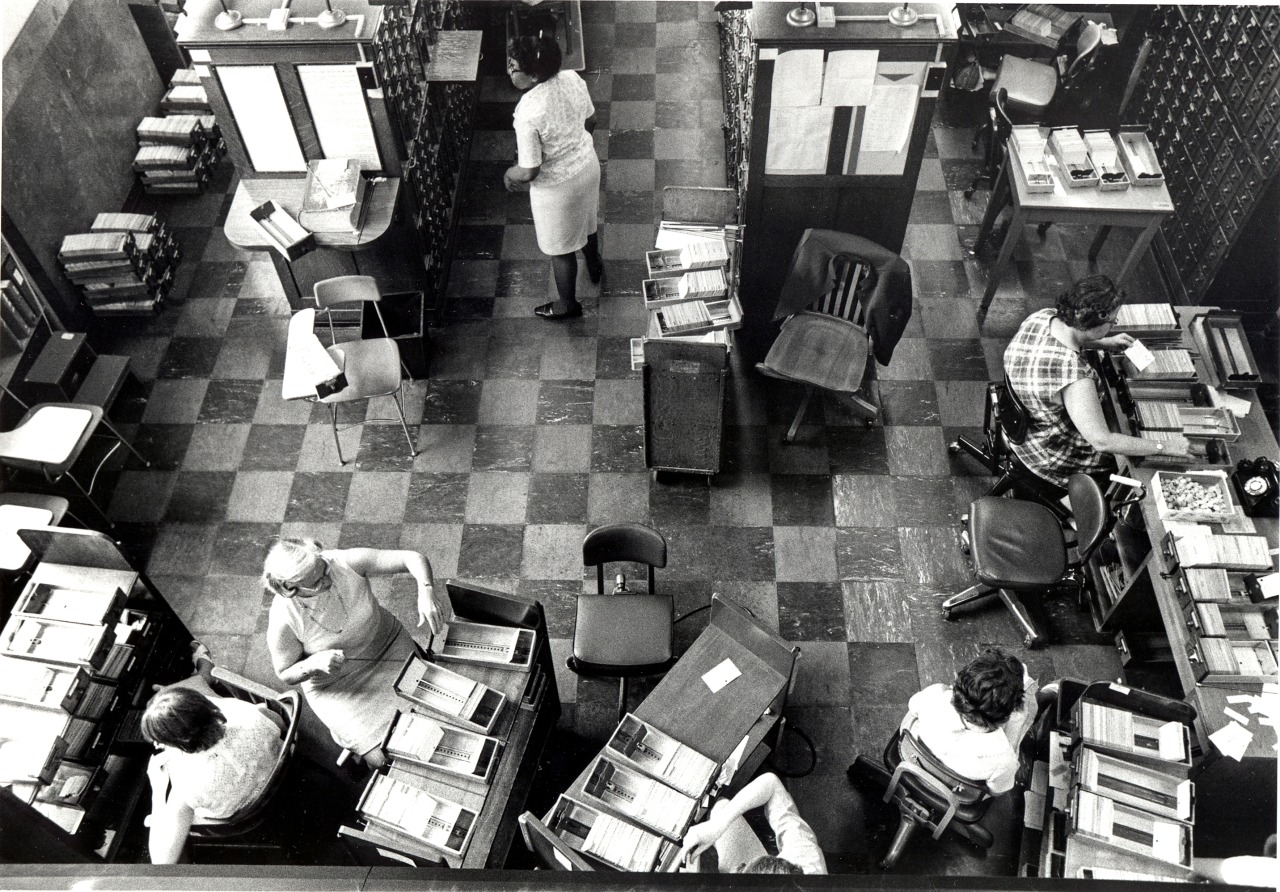 Black and white photograph of the Catalog Department, this time of the Workroom area, taken in 1973