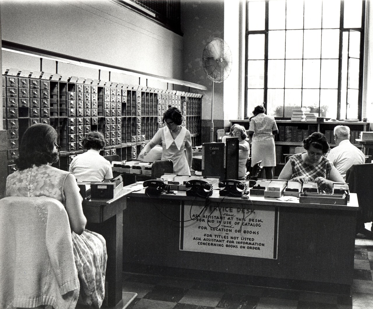 Black and white photo of the Service Desk/Workroom area, also from 1973.