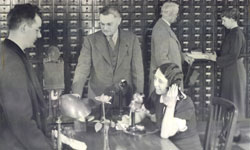 A female librarian on a phone with men standing behind her in suits looking at the card catalog. Black and white photo.
