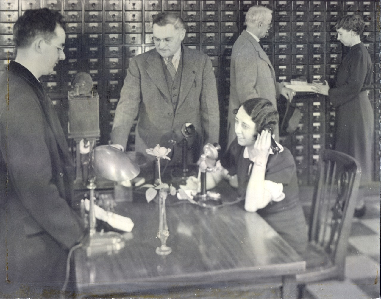 Black and white of female librarian on the phone at a table in front of 3 men and the wall-size card catalog.
