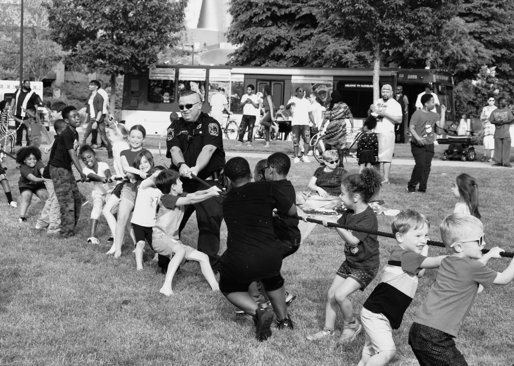 children's tug of war contest with cop playing