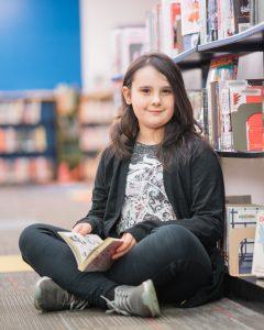 Jaylyn sitting down reading by a bookshelf