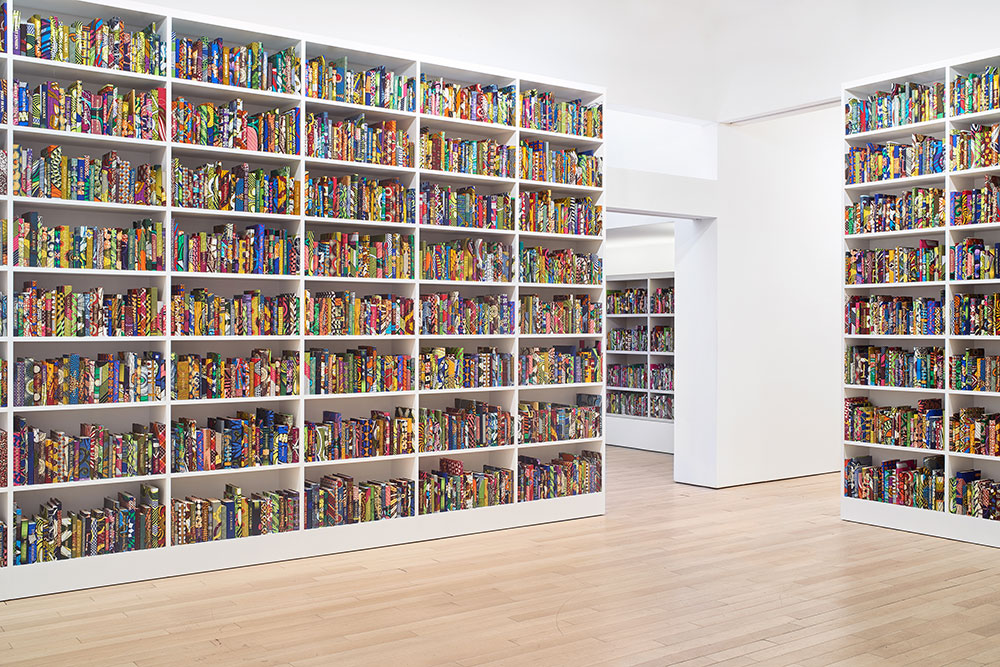 Yinka Shonibare's past work shown in a photograph of many books on bookshelves spanning multiple rooms.
