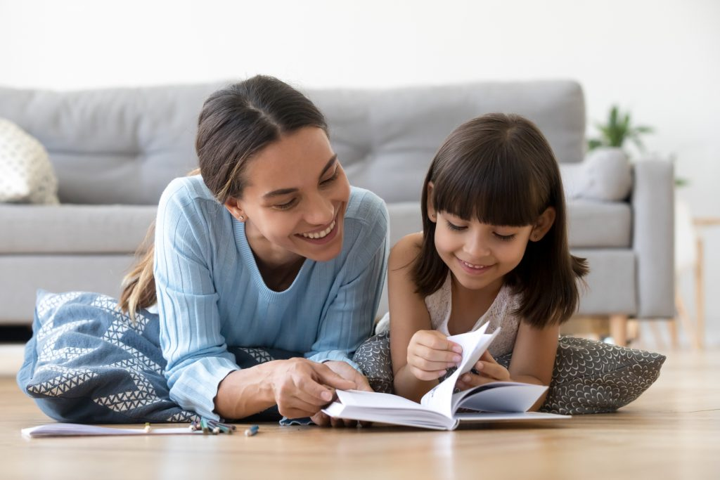 Caring smiling mother reading book with little kid girl lying on warm floor at home.