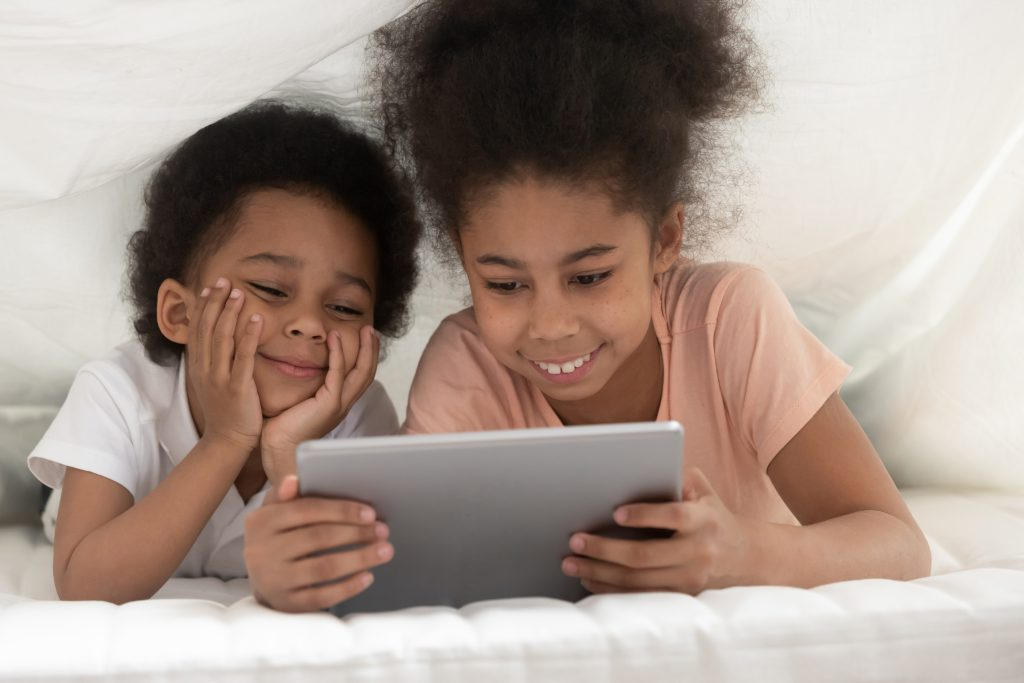 Smiling cute, young sister and brother lying under white blanket watching tablet together.