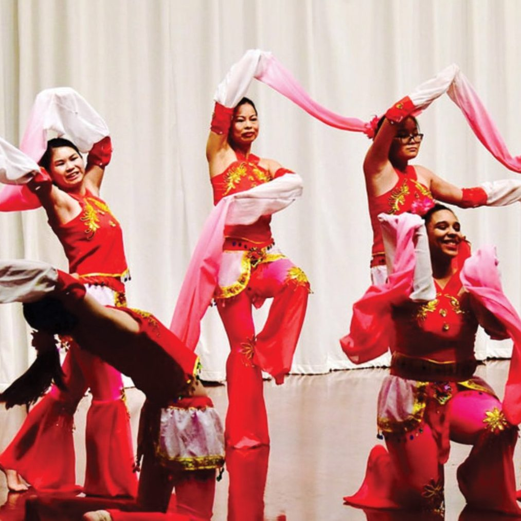Photography of people in tradition red costumes with scarves, dancing on stage.
