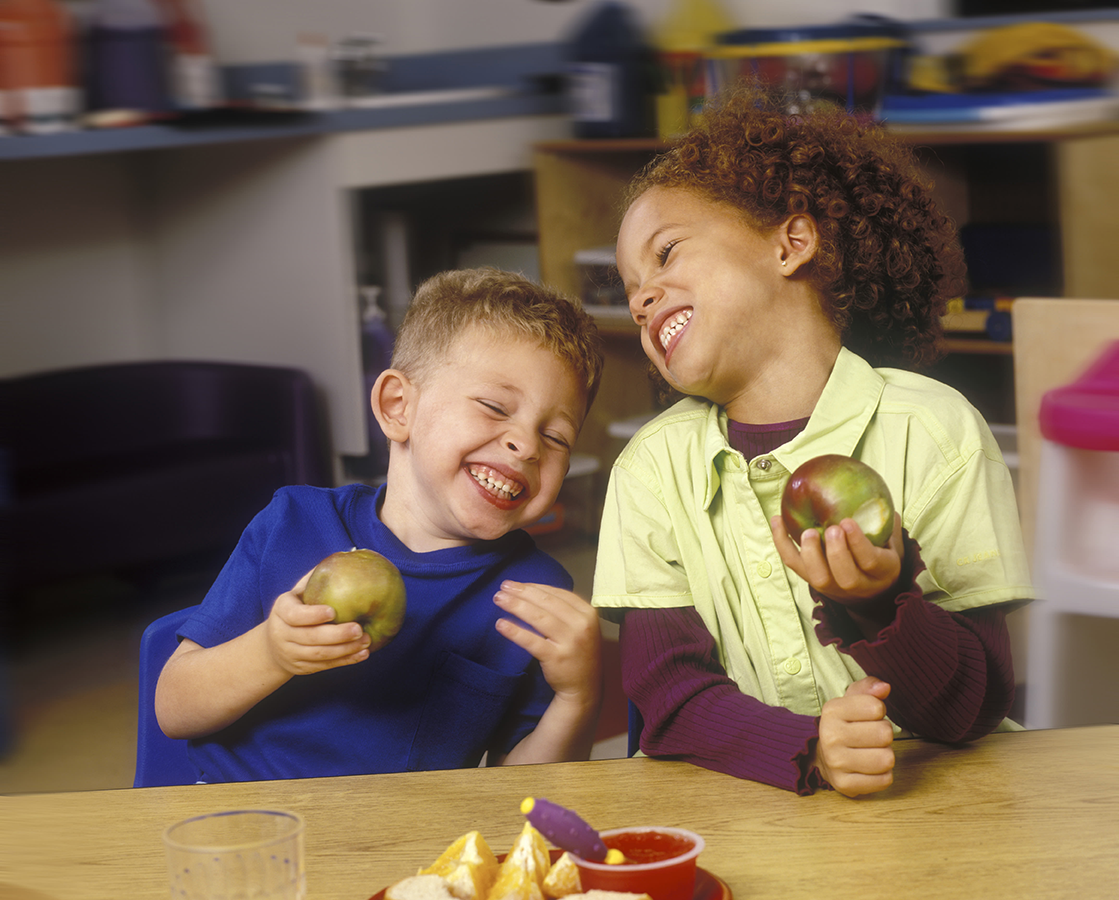 A young caucasian boy and an brown-skinned girl eating apples at a table and laughing wildely.