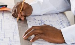 A man's hands drawing a blueprint on a drafting table.