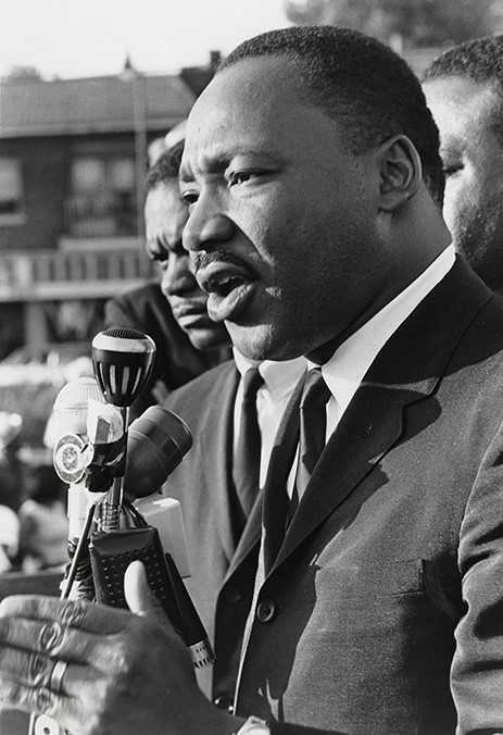 Martin Luther King, Jr. speaking at a microphone in front of a crowd.
