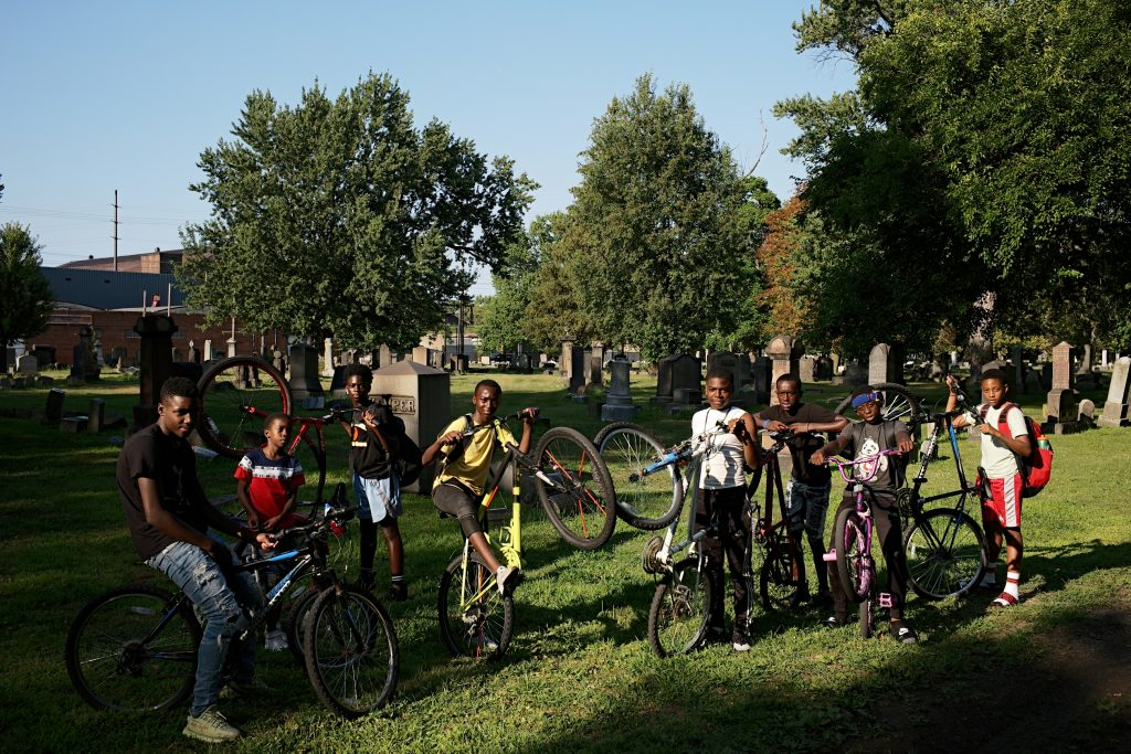 large group of boy with bikes stand in a cemetery facing camera