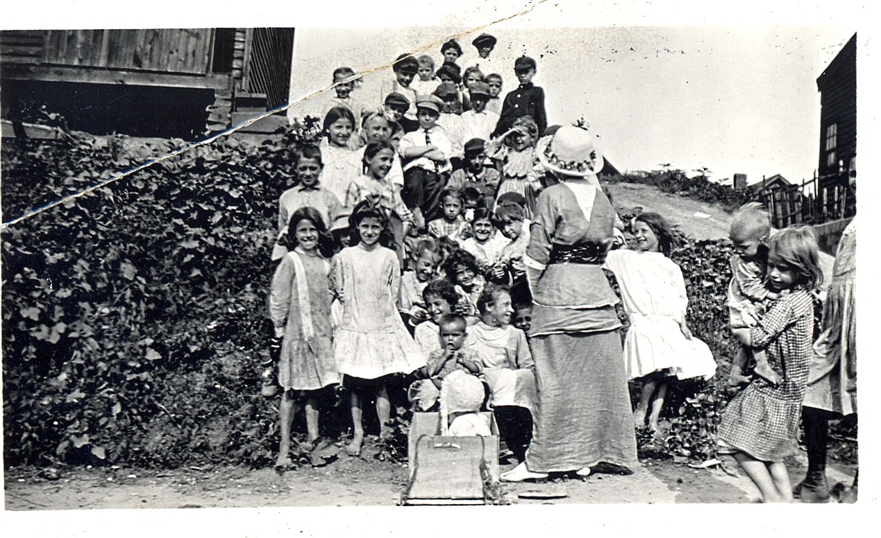 Group of children standing on a hill for open-air story hour from around 1910.