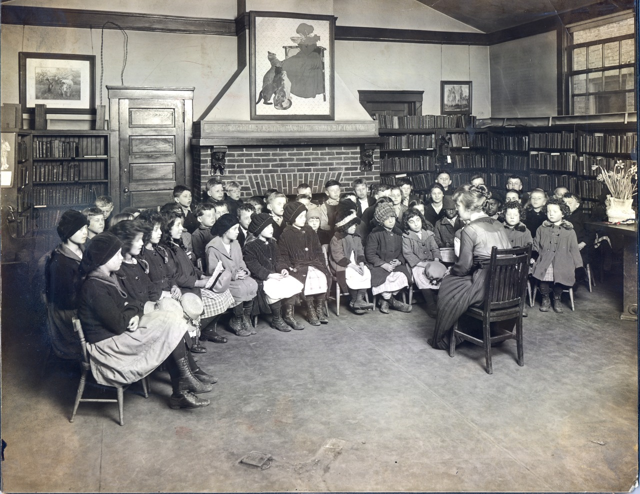 Black and white photo of children in chairs in a semicircle around a librarian reading from a book.
