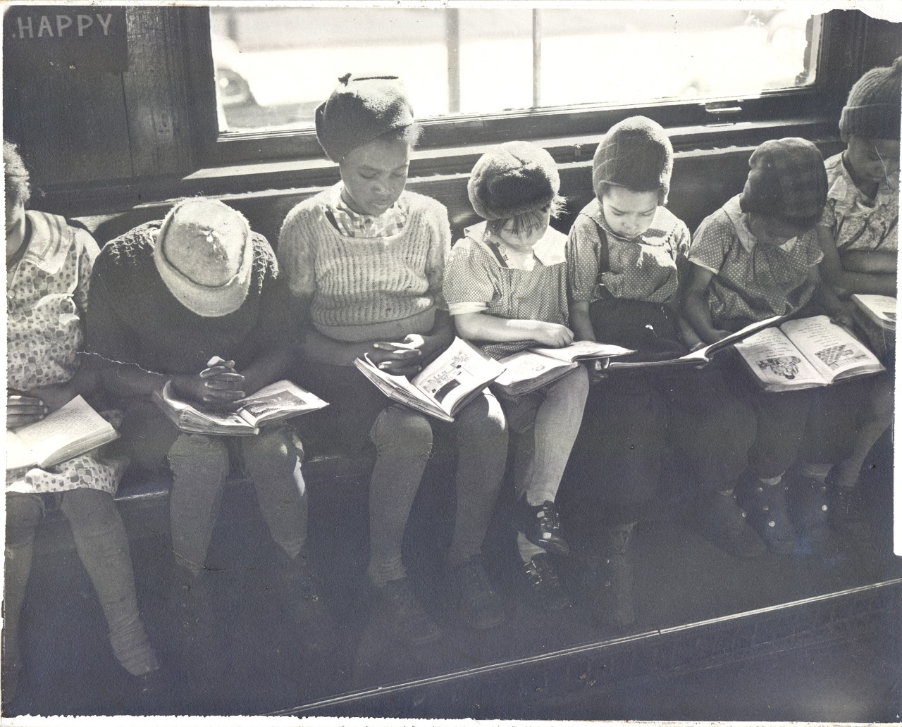Black and white photo of children reading at the Quincy Branch in 1937