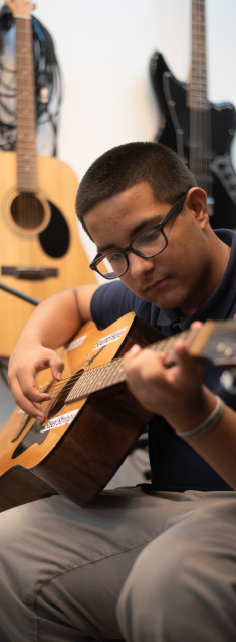 Joswen Colon playing guitar in South Branch's sound booth
