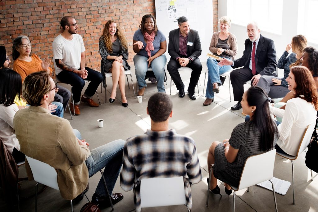 Community members sitting in a circle while having a group discussion