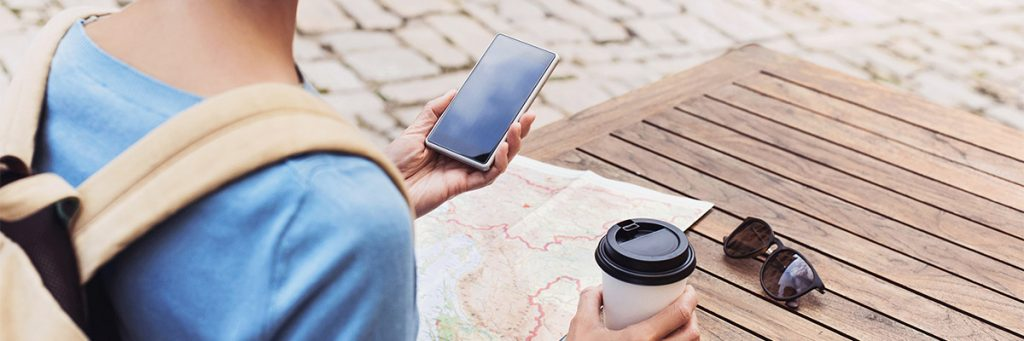 Picture of a young traveler looking at her cellphone while holding a cup of coffee. A map and a pair of sunglasses are on the table in front of her.