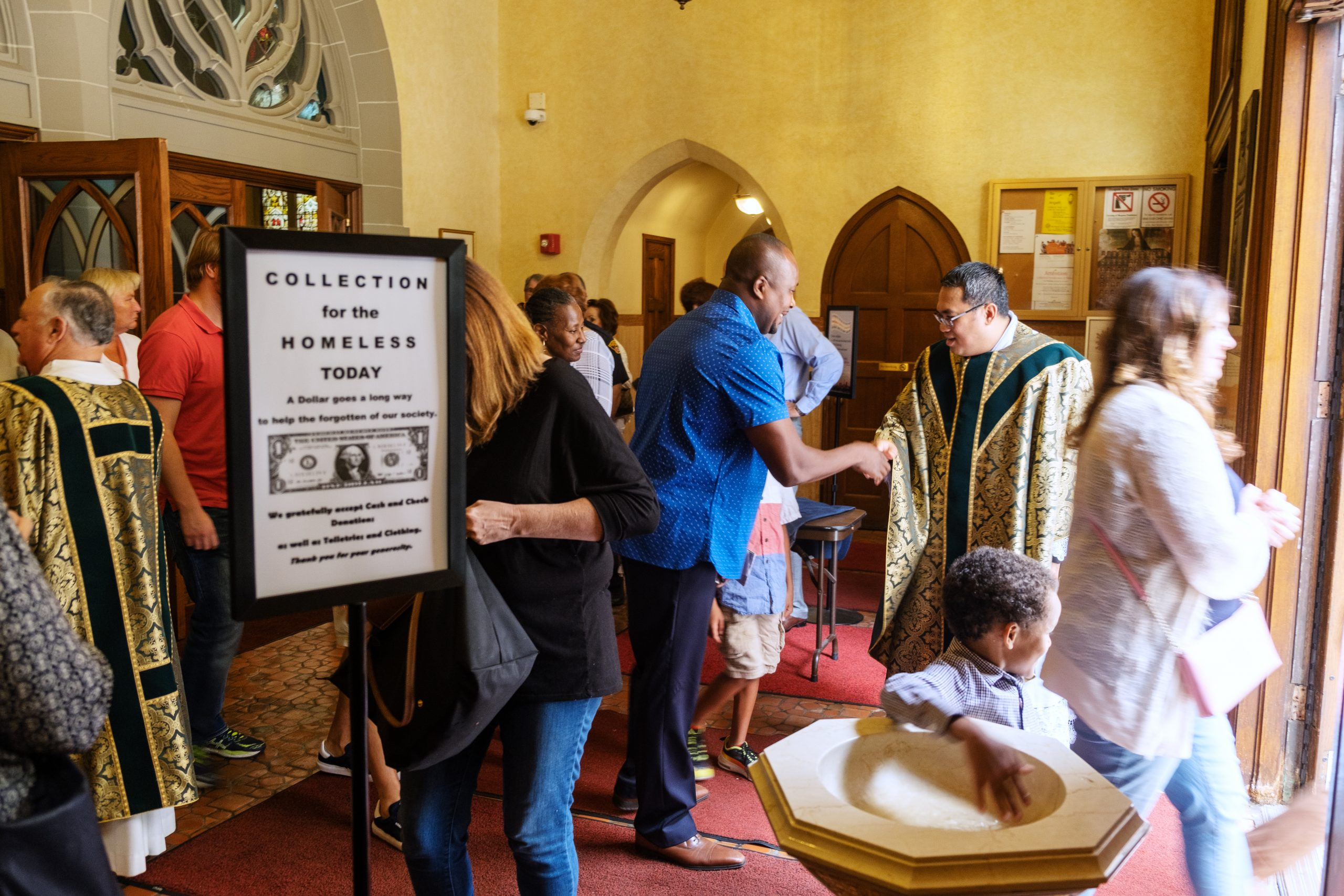 "People in the entrance of a church and a sign that reads ""Collection for the Homeless Today"""